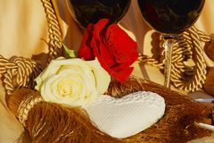 Heart, roses, play of golden hues, background. White flowery heart, glasses of red wine and red rose on golden textile hues. Love and romantic concept. Valentine stock photography