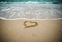 Heart on the sand. A heart drawn on the sand, it will be gone in a few moments. This moment is a symbol of love and time because only time is capable of Stock Images