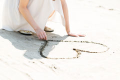 Heart on the sand. Woman on the beach making heart on the sand Stock Photography
