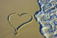 Heart in the sand. A heart drawn on the beach, in the low evening light, about to be washed away by a wave Royalty Free Stock Photo