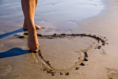 Heart in the sand. Girl drawing an heart in the sand Stock Photography