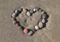 Heart on sand. Heart which is laid out from stones on sea sand Royalty Free Stock Photos