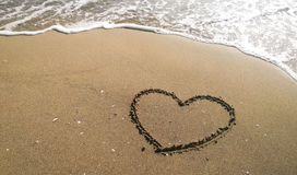 Heart on the sand beach. Conceptual design. Heart on the beach, hand drawing on sand on the sea Stock Image