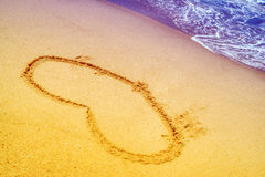 Heart in sand at the beach Stock Images