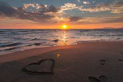 Heart in sand on beach at sunset Royalty Free Stock Photos