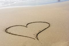 A heart in the sand on a beautiful beach in the sunshine with space for further editing stock images