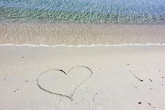 Drawing heart on sand Stock Photography