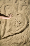 Heart in the sand and the hand of child Stock Image