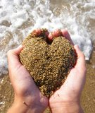 Heart of sand in hands. Heart made of sand in child hands above the sea foam stock photos