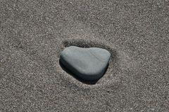 A heart in the sand. A heart shaped rock sitting in perfectly smooth sand on a sunny day at the beach Stock Photography