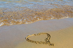 Heart in the sand at sunset Stock Images