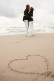 Heart on the sand two young lovers kissing Stock Images