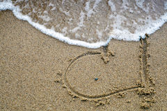Heart on the sand and wave Stock Images
