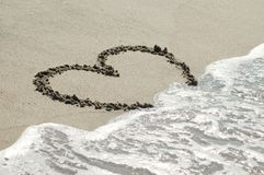 Heart on sand with wave approaching Royalty Free Stock Images