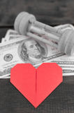 Heart, sandglass & banknotes Stock Photo