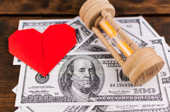Heart, sandglass & banknotes Royalty Free Stock Photography