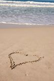 A heart on sandy beach. Drawing of a heart on sandy beach with ocean full of waves in the background stock images