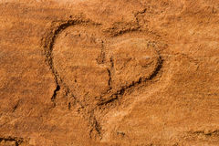 Heart scraped into sandstone Stock Images