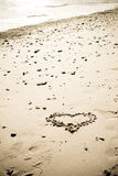 Heart scratched into the sand Stock Photography