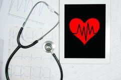 Heart on screen touch pad and stethoscope. Cardiogram chart Stock Photos