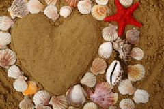 Heart from the sea shells and sand Stock Photo