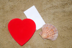 Heart, seashell and paper on the beach Stock Photo