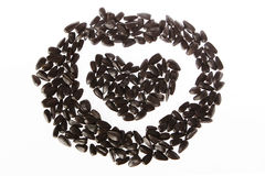 Heart seeds. Black sunflower seeds Laid heart Royalty Free Stock Images