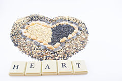 Heart and seeds. Different seeds in the form of heart and with chips written the word heart Stock Images