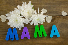 Heart shape with alphabet reading mama and white flowers Stock Photo