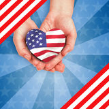 Heart shape American flag. Digitally generated image of hands holding heart shape American flag Stock Images