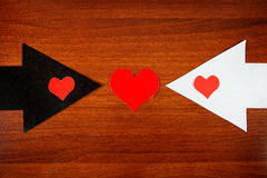 Heart Shape on the Arrow. Heart Shapes on the Black and White Arrows on the Wooden Background Royalty Free Stock Photos