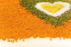 Heart shape background made of mixed wheat grains, white salt, g Stock Photo