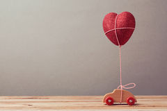 Heart shape balloon and car toy on wooden table. Valentine's day concept. Stock Image