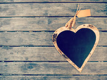 Heart shape black board on wooden wall. Vintage color filtered, love concept background Stock Photography