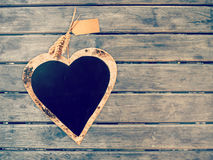 Heart shape black board on wooden wall. Vintage color filtered, love concept background Royalty Free Stock Photos