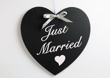 Heart shape blackboard with white hearts ribbon against a white background with Just Married message. For weddings or honeymoons Royalty Free Stock Images