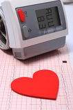 Heart shape and blood pressure monitor on electrocardiogram Stock Photo