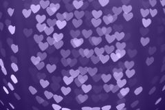 Heart shape blurred bokeh background with sparkles. Ultra violet. Heart shaped holiday blurred bokeh background with sparkles. Valentine background. Christmas Stock Photography