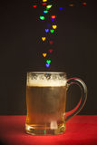 Heart shape bokeh lights floating out of beer glass Royalty Free Stock Photos