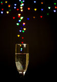 Heart shape bokeh lights floating out of Champagne glass Royalty Free Stock Photos