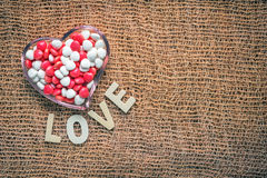 Heart shape bowl of color candy. And wooden letter love on fabric background stock photography