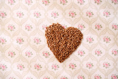 Heart shape of buckwheat cereals. Heart shaped buckwheat cereals on a serviette with flowers Stock Photos