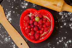 Heart shape cake with fresh raspberries. Red heart shape cake with fresh raspberries and other berries and wooden rolling pin, dark background, close up Royalty Free Stock Photography