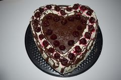 Heart shape cake. Poppy cream cake with white topping and cherry on top, product photography for patisserie. Chocolate, sugar. stock photos