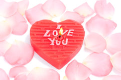 Heart-shape candle and rose petals Royalty Free Stock Image