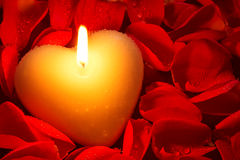Heart shape candle and rose petals. A heart shape candle surrounded by red rose petals covered in water droplets, a good image for a Valentines day or other Stock Image