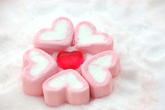 Heart shape candy around by marshmallows on snow royalty free stock images