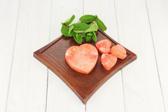 Heart shape carved from the pulp of watermelon with mint sprigs Stock Photography