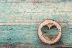 Heart shape carved in wood cut on the old turquoise boards. Stock Photography