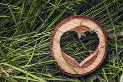 Heart shape carved in wood lies on a green grass. Stock Photo